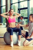 sport, fitness, lifestyle and people concept - smiling man and woman with exercise ball in gym