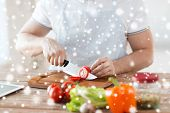 cooking, people, vegetarian food and home concept - close up of man chopping tomato and other vegetables on cutting board with big knife