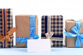 Gift boxes with greeting card on light blue uneven background