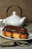 Tasty eclairs and pot of tea on wooden table