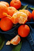 Fresh ripe mandarins on blue fabric background
