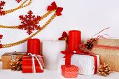 Christmas candles on shelf on white wall background