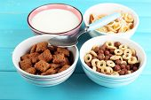 Various sweet cereals in ceramic bowls and bowl with milk on color wooden background