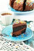 Chocolate cake with colorful sweet powder on table close-up