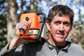 foto of man chainsaw  - A man with a chainsaw slung over his shoulder takes a break from the yard clean - JPG
