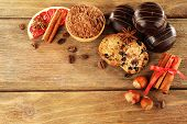 Chocolate cookies with bowl of cocoa, nuts, coffee beans, slice of grapefruit and cinnamon on rustic background