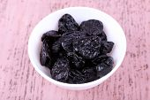 Bowl with heap of prunes on color wooden background