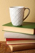 Pile of books with cup on wicker surface and light wall background