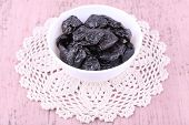 Prunes in bowl on lace doily on color wooden background