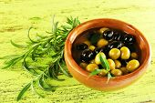 Black and green olives with leaves in bowl on painted wooden background