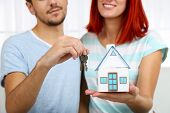 Loving couple sitting in sofa and holds toy house and keys