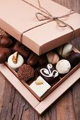 Box filled with chocolates on wooden rustic background
