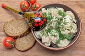Russian Cuisine: Dumplings On A Plate, Cherry Tomatoes And Bread On A Wooden Background.