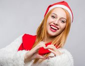 Beautiful young woman with Santa hat smiling gesturing a heart.