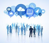 Group of business people in a white background with colorful speech bubbles above containing social networking symbols.