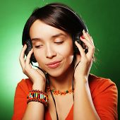 Young happy woman with headphones listening music