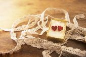 Strip of white lace and golden box with two hearts on a wooden work table. warm lighting.