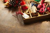Christmas preparation scene. Wooden tray with ribbons and christmas tags, on an old wooden table with vintage feel.