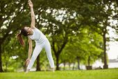 Full length of toned young woman doing stretching exercises in park