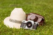 Vintage camera with his cover near a straw hat on the grass