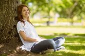 Pretty redhead sitting in casual clothing in park on a sunny day