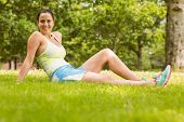 Happy fit brunette sitting and relaxing on the grass in the park
