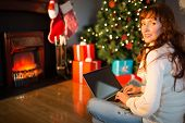 Redhead woman sitting on floor using laptop at christmas at home in the living room