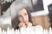 Brunette in white wool jumper thinking against fir tree forest and snowflakes
