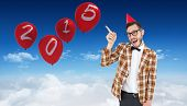 Geeky hipster in party hat pointing against bright blue sky over clouds
