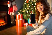 Pretty redhead woman showing you mobile phone at christmas at home in the living room
