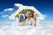 Happy extended family waiting for barbecue being cooked by father against bright blue sky with clouds