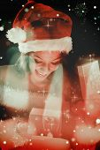 Pretty brunette in santa outfit opening gift against candle burning against festive background