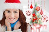 Festive redhead against blurry christmas tree in room