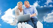 Happy mature couple using laptop against cloudy sky