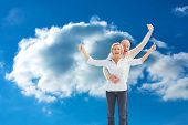 Happy mature couple cheering at camera against cloudy sky