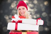 Festive blonde holding pile of gifts against shimmering christmas tree of lights