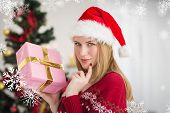 Festive woman standing holding a pink gift against snowflakes