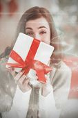 Brunette showing gift on the couch at christmas against christmas light design
