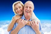 Happy mature couple embracing smiling at camera against blue sky over clouds