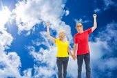 Mature couple walking and holding hands against bright blue sky with clouds