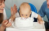 Kid eats cake. Family celebrates the first birthday of his son.