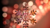 Hanging snowflake against light circles on black background
