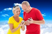 Happy mature couple looking at smartphone together against bright blue sky with clouds