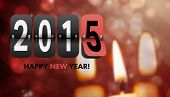 Happy new year 2015 against candle burning against festive background