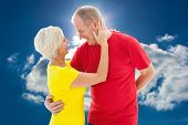 Happy mature couple hugging and smiling against blue sky with clouds and sun