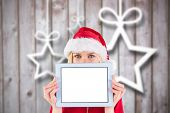 Festive blonde holding a tablet pc against blurred christmas background