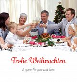 Family drinking a toast in a Christmas dinner against christmas greeting in german