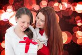 Mother and daughter with gift against twinkling red and orange lights