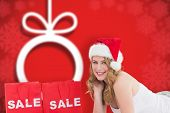 Festive blonde with sale shopping bags and present against blurred christmas background