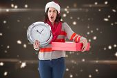 Surprised brunette holding a clock and gift against blurred lights